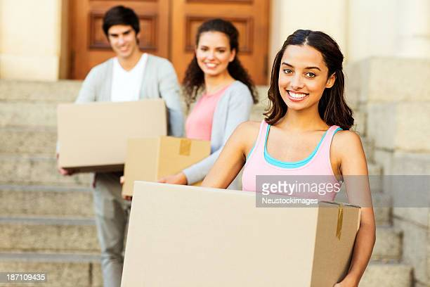 Girl Carrying Cardboard Box With Friends Standing In Background