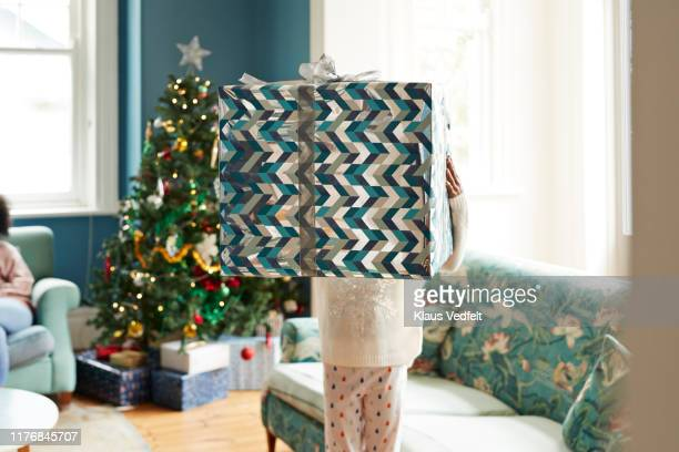 girl carrying christmas present at home - personne secondaire photos et images de collection