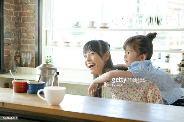 Girl carrying daughter on back in kitchen
