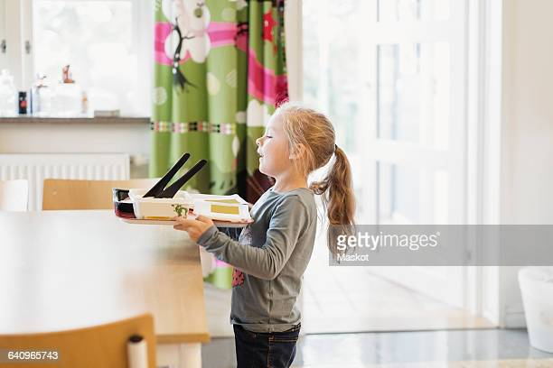 Girl carrying food tray in preschool