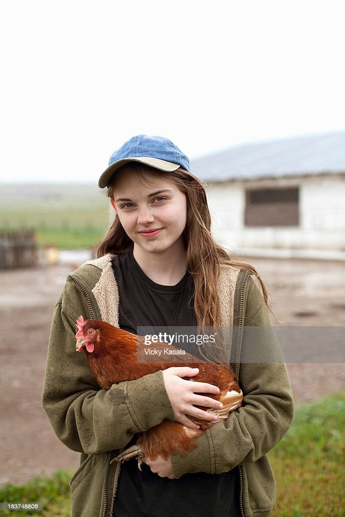 Girl carrying hen : Stock Photo