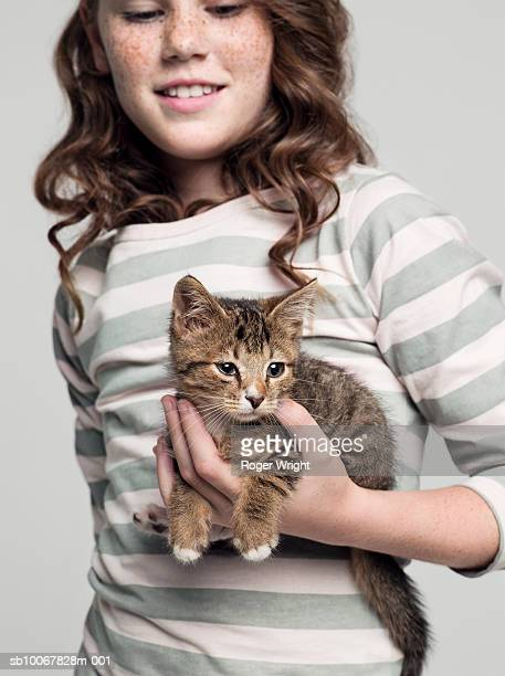 girl (8-9 years) carrying kitten in hand, studio shot - einzelnes tier stock-fotos und bilder