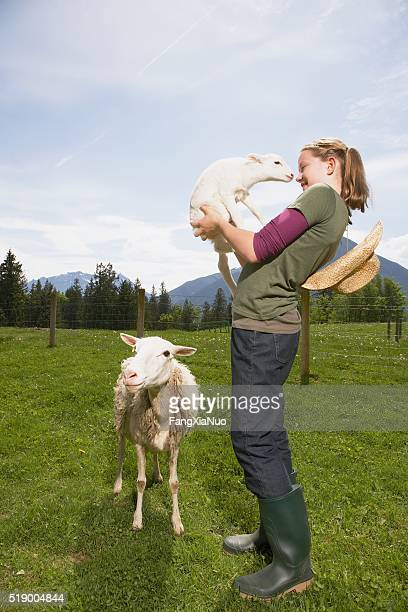 Girl carrying lamb on farm