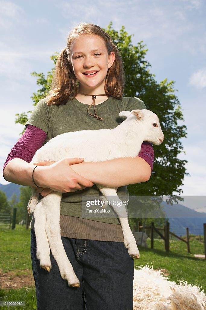Girl carrying lamb on farm : Stock Photo