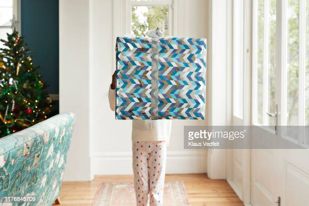 Girl carrying large Christmas present at home