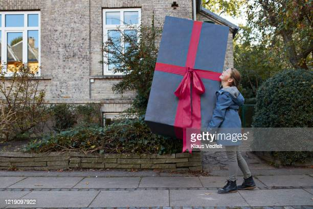 girl carrying large gift box on footpath in city - large stock pictures, royalty-free photos & images