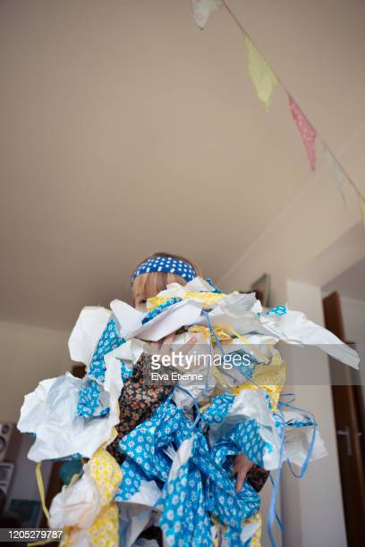 girl (6-7) carrying large pile of discarded gift wrapping paper after a birthday celebration - messy house after party stock pictures, royalty-free photos & images
