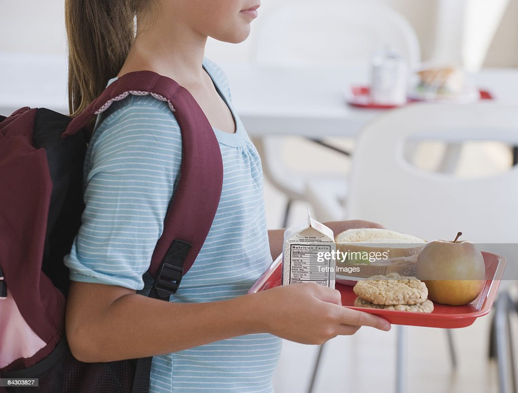 Girl carrying lunch tray at school : Stock Photo