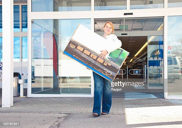 girl carrying new-bought tv out of store - electronics store stock photos and pictures