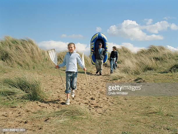 Girl (7-9) carrying oars, man carrying inflatable boat by son (11-13)