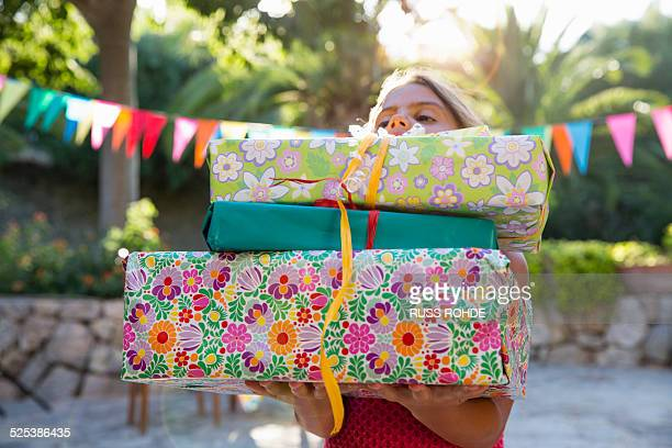 Girl carrying pile of birthday presents