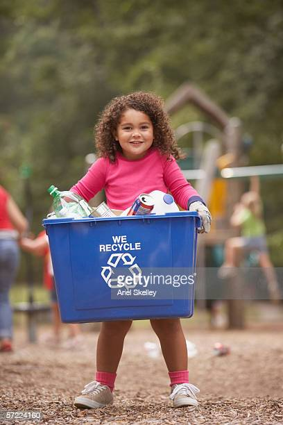 Girl carrying recycling container