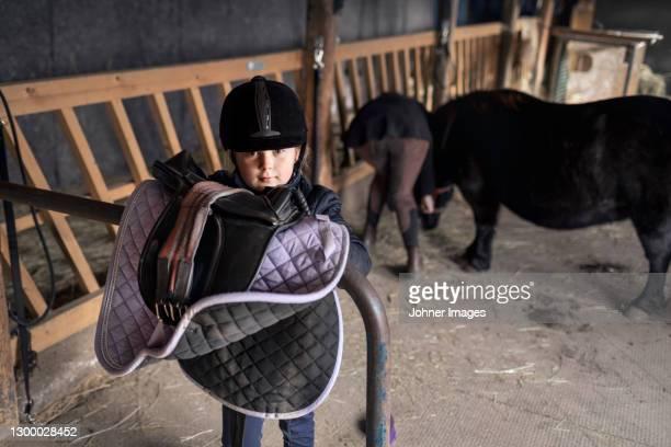 girl carrying saddle in stable - incidental people stockfoto's en -beelden