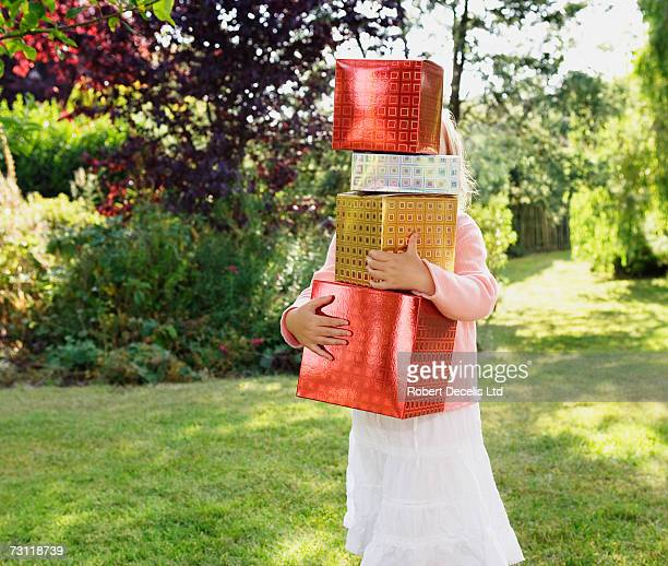 Girl (4-5) carrying stacked presents in garden