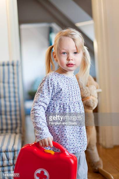 girl carrying toy first aid kit - kids first aid kit stock pictures, royalty-free photos & images