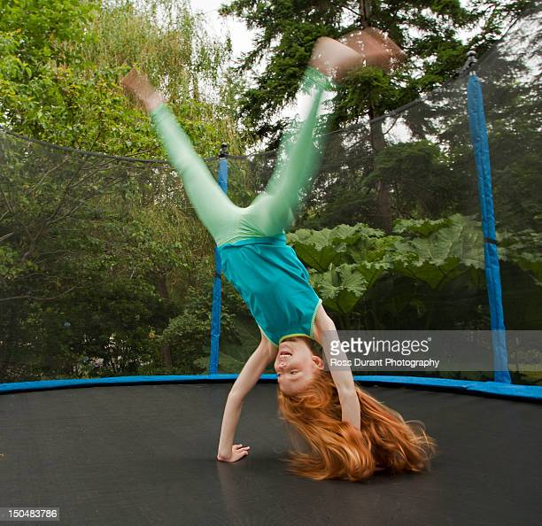 a girl cartwheeling on a trampoline in a garden - girl with legs spread stock photos and pictures
