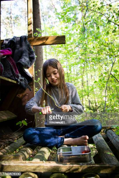 girl carving a piece of wood sitting on raised hide in the woods - carving knife stock pictures, royalty-free photos & images