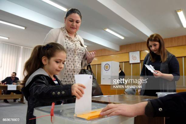 A girl casts a ballot at a polling station in Yerevan on April 2 as Armenians vote for legislative elections for the first time since the adoption of...