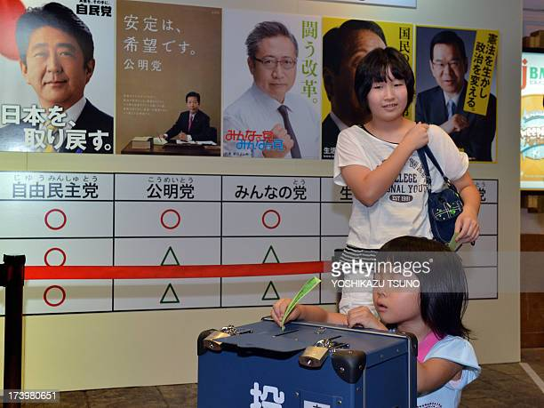 A girl casts a vote in a straw poll near posters of Japan's major parties including ruling Liberal Democratic Party leader and Prime Minister Shinzo...