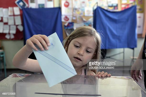 A girl casts her father's vote in a polling station in Athens for the European elections and the second round of the local elections on May 25 2014...