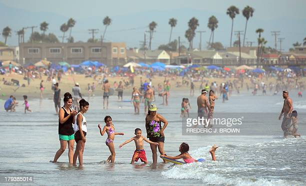 A girl catches a wave on her boogie board for her family to see as crowds took to southern California beaches on the Labour Day holiday on September...