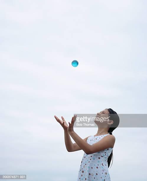 Girl (10-12) catching ball, smiling