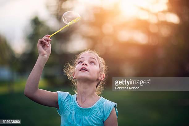 girl catching bubble on bubble wand