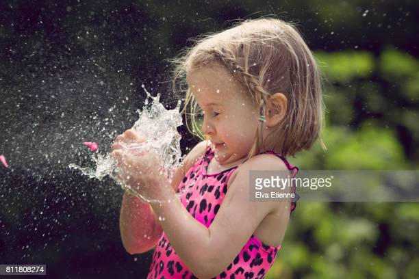 Girl (4-5) catching bursting water balloon