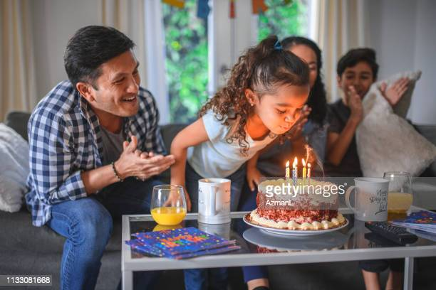 girl celebrating birthday with family at home - family at home stock photos and pictures