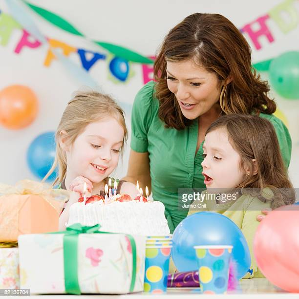 Girl celebrating birthday with mother and sister