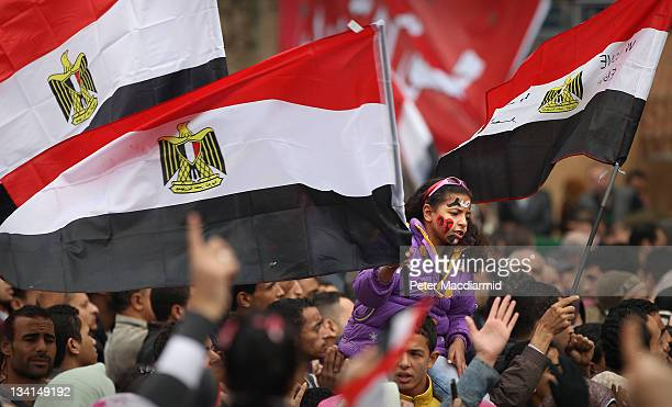 A girl chants and waves a flag as she and other protestors remain in Tahrir Square on November 27 2011 in Cairo Egypt Protestors are continuing to...