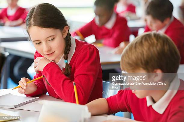 "girl cheating from boys work in classroom - ""compassionate eye"" stock pictures, royalty-free photos & images"