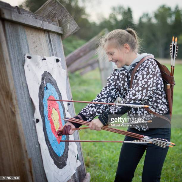 Girl (10-12) checking bull's eye for her score in bow shooting