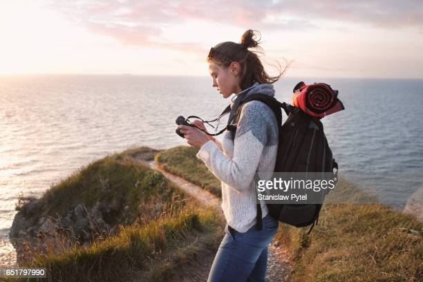 Girl checking camera near ocean