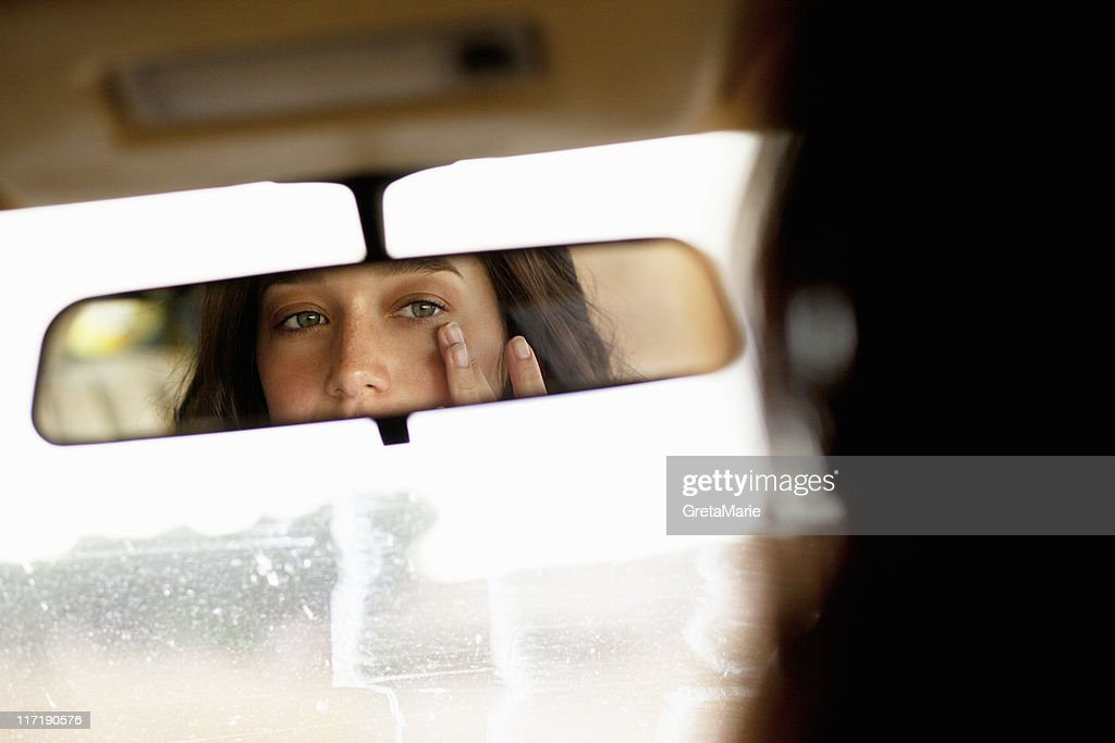 Girl checking in mirror : Stock Photo