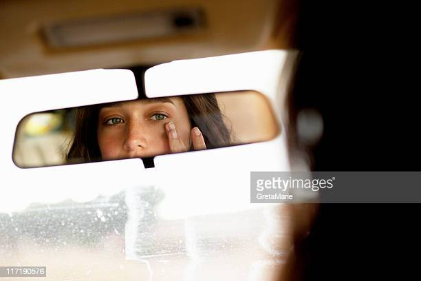 girl checking in mirror - vehicle mirror stock photos and pictures