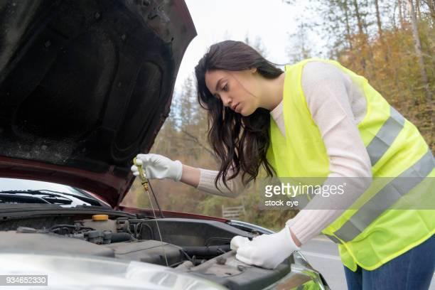 Girl checking level of new engine oil