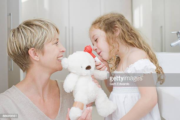 Girl checking stuffed animals ear with otoscope