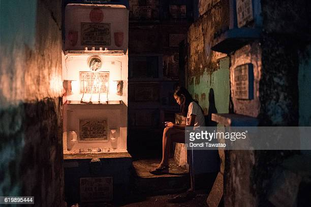 A girl checks her phone inside a cramped public cemetery on November 1 2016 in Manila Philippines as Filipinos flock to cemeteries around the country...