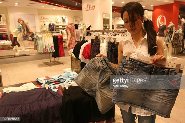 A girl checks out a skirt at a shop in New Delhi on June 23 2010