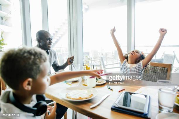 Girl cheering at table in restaurant