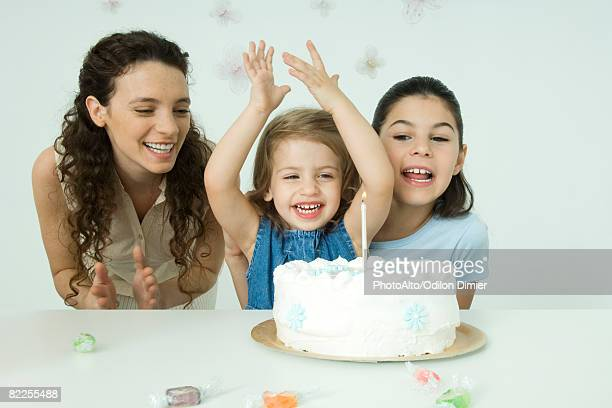 Girl cheering behind birthday cake, mother and sister watching