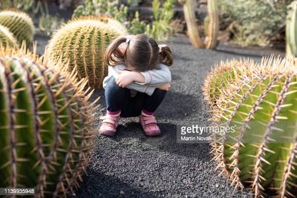 Girl child hiding her face. Sitting in between cactuses.