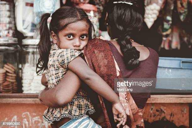 Girl child hold by her mother at the grocery shop in a slum of Chennai Tamil Nadu India