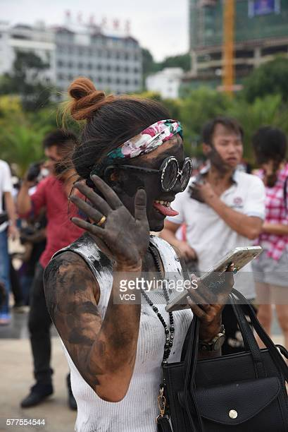 Girl child is daubed rice ash on face during the Face Painting Festival in Puzhehei Resort of Qiubei County on July 18, 2016 in Wenshan Prefecture,...