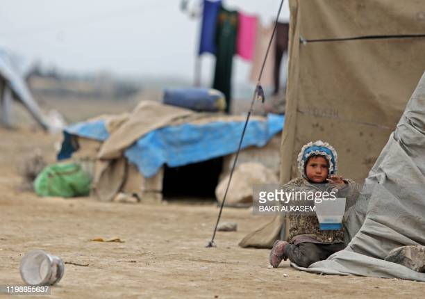 Girl child outside a tent at a camp where displaced Syrian families from the south of Aleppo are taking refuge, in the vicinity of the northern...