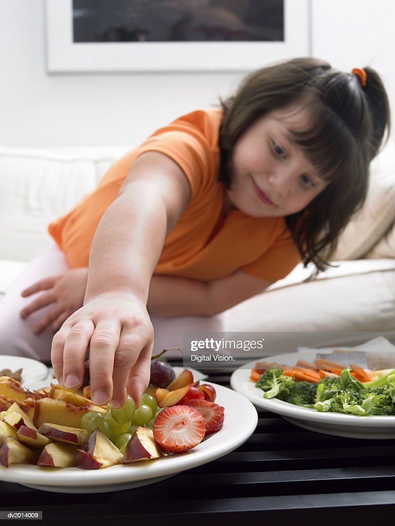 Girl Choosing a Grape from a Plate of Fruit : Stock Photo