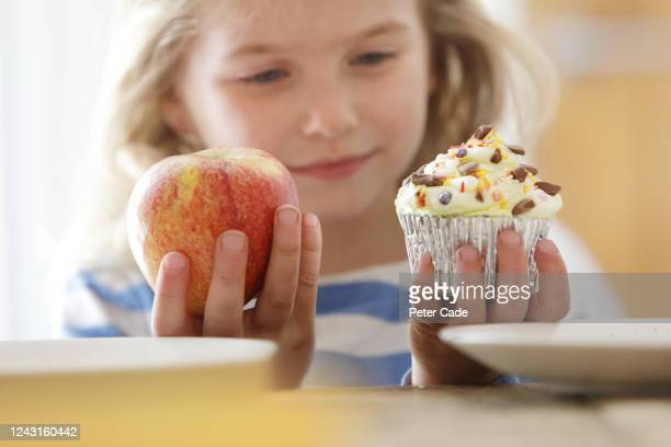 girl choosing between an apple and a cake - unhealthy eating stock pictures, royalty-free photos & images