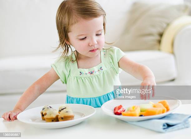 Girl (2-3) choosing between fruit salad and muffins