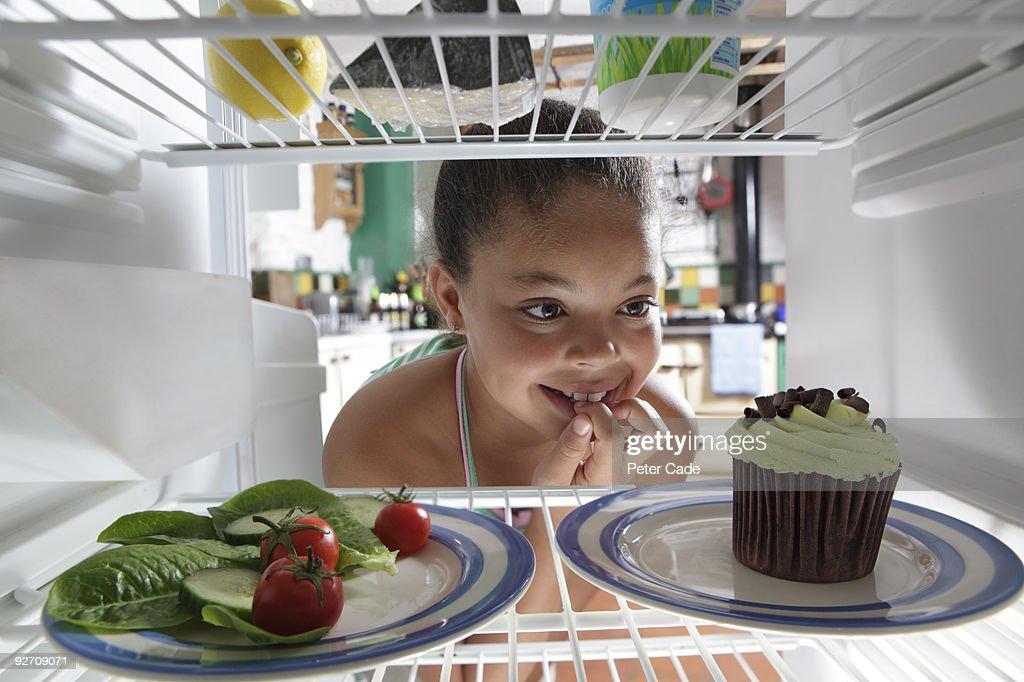 girl choosing between salad and cake : Stock Photo